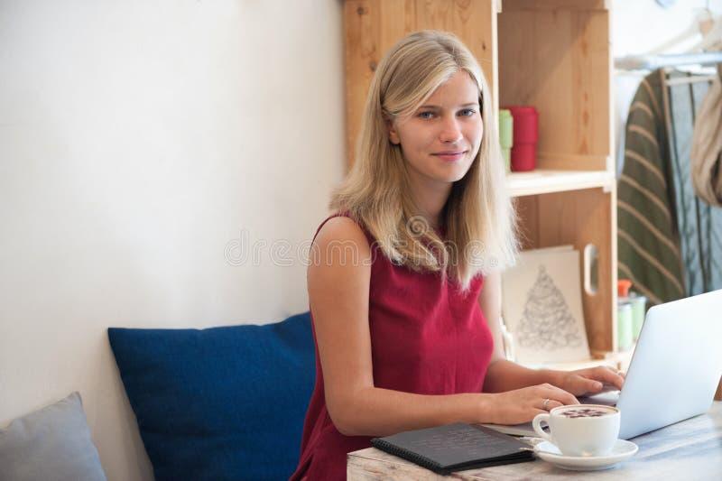 Mujer rubia joven que mecanografía en ordenador portátil en café fotografía de archivo