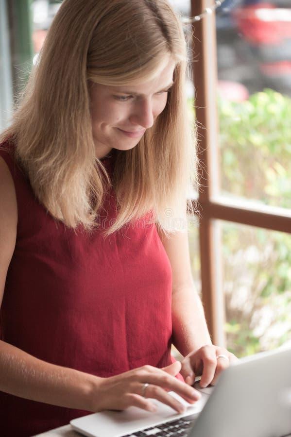 Mujer rubia joven que mecanografía en ordenador portátil en café fotos de archivo