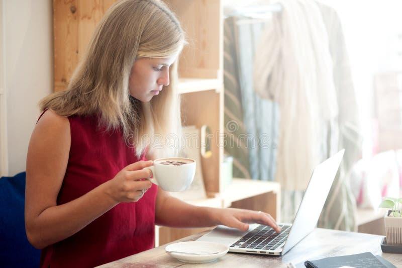 Mujer rubia joven que mecanografía en ordenador portátil en café fotos de archivo libres de regalías