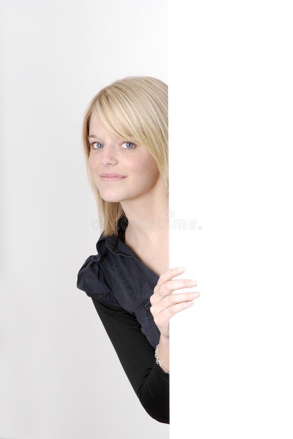 Mujer rubia joven que mira de detrás un anuncio foto de archivo libre de regalías