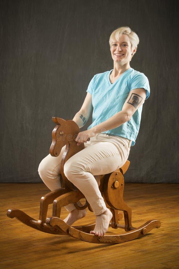 Mujer rubia joven que monta el caballo mecedora de madera en el estudio fotos de archivo libres de regalías