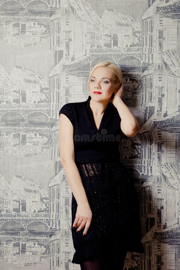Mujer rubia joven que presenta en vestido negro foto de archivo libre de regalías
