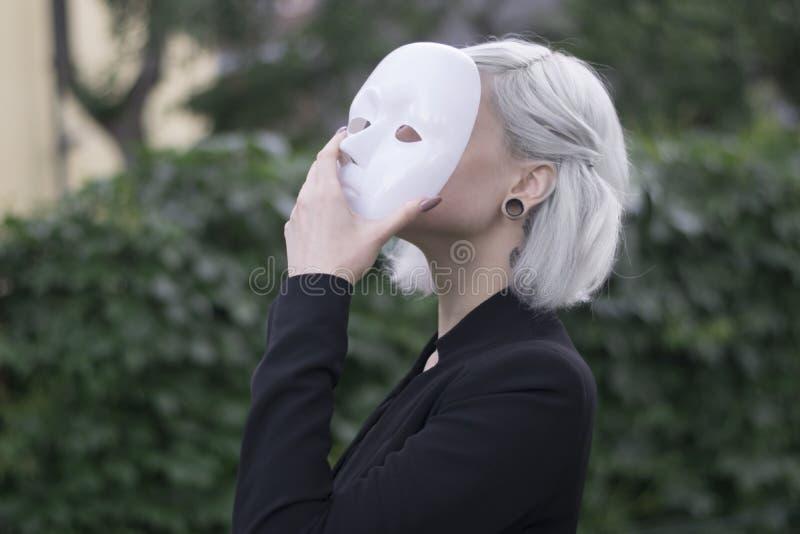 Mujer rubia joven que saca una máscara Fingimiento ser algún otro concepto outdoors imagen de archivo libre de regalías