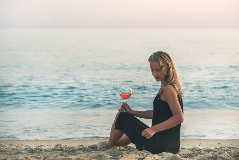 Mujer rubia joven que se sienta con el vidrio de vino rosado en la playa por el mar en la puesta del sol imagen de archivo