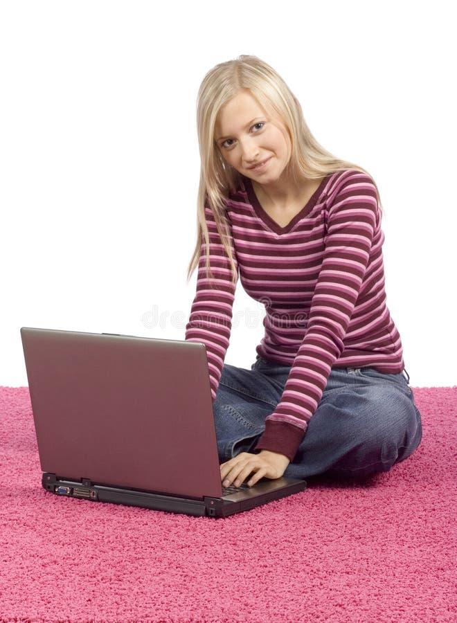 Mujer rubia joven que se sienta en la alfombra rosada con la computadora portátil fotografía de archivo