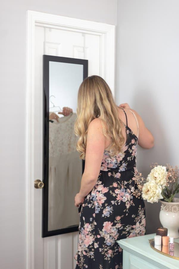 Mujer rubia joven que soporta el vestido que mira en el espejo foto de archivo
