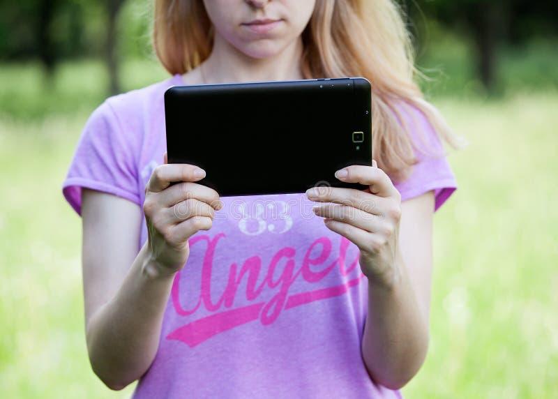 Mujer rubia joven que sostiene una tableta al aire libre imagen de archivo