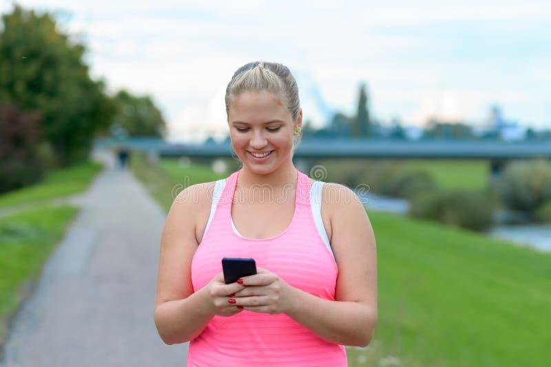 Mujer rubia joven que usa el teléfono móvil al aire libre foto de archivo libre de regalías