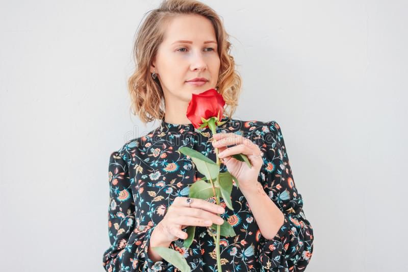 Mujer rubia joven romántica hermosa en vestido con la rosa roja en el fondo blanco aislado fotos de archivo