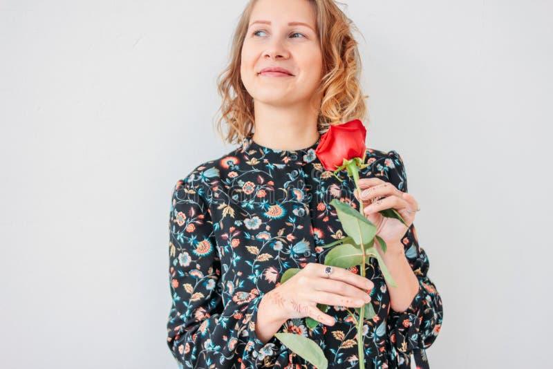 Mujer rubia joven romántica hermosa en vestido con la rosa roja en el fondo blanco aislado foto de archivo