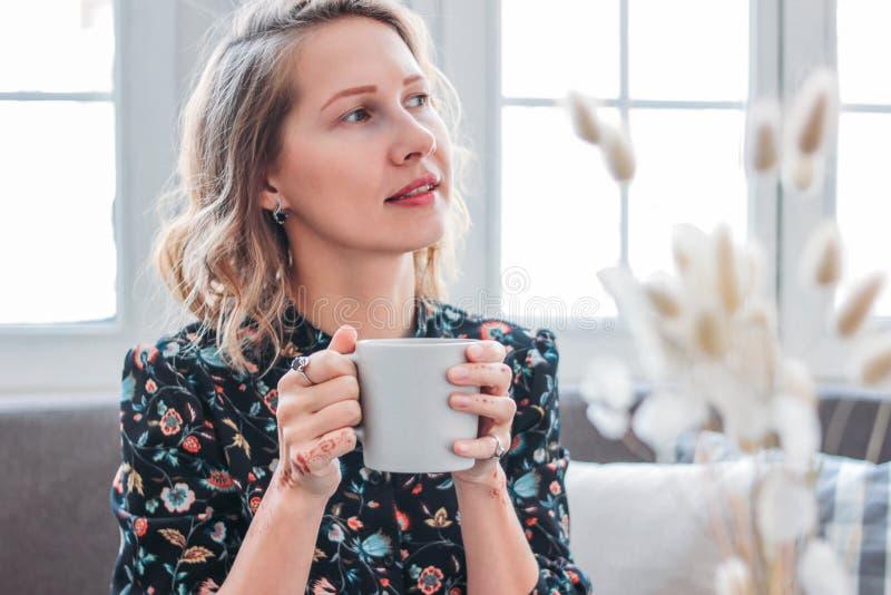 Mujer rubia joven romántica hermosa en vestido con la taza de té que se sienta por la ventana Joyería femenina, mehendi fotos de archivo libres de regalías
