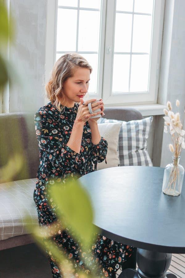 Mujer rubia joven romántica hermosa en vestido con la taza de té que se sienta en la tabla por la ventana foto de archivo