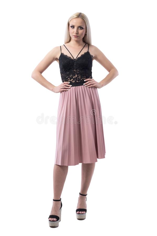 Mujer rubia joven seria descontentada en ropa elegante del verano con las manos en las caderas que miran la cámara foto de archivo