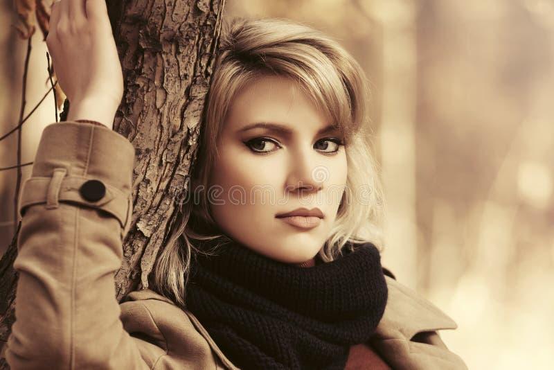 Mujer rubia joven triste de la moda en capa clásica beige al aire libre foto de archivo