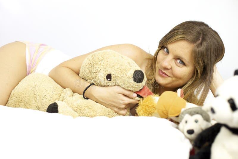 Mujer rubia linda en la cama que pone con muchos juguetes rellenos fotos de archivo libres de regalías