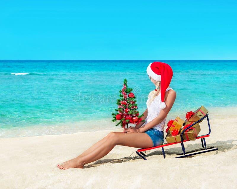 Mujer rubia linda en la playa del mar en el sombrero de santa que se sienta en el trineo con imagen de archivo libre de regalías