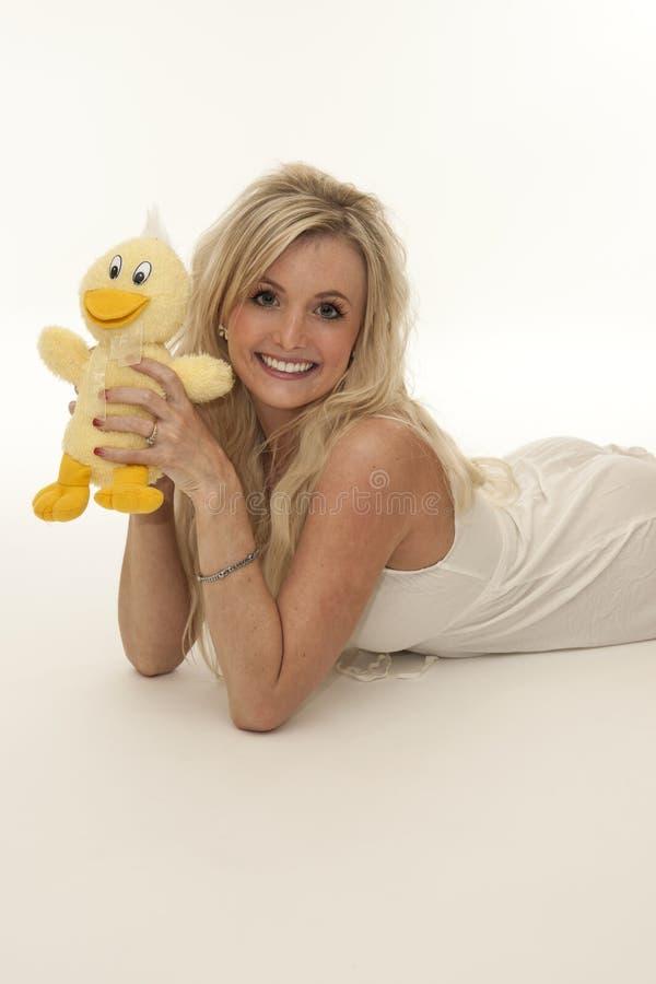 Mujer rubia linda feliz con el pato del juguete imagen de archivo