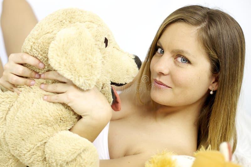 Mujer rubia linda feliz con el perro de juguete relleno imágenes de archivo libres de regalías