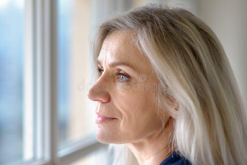 Mujer rubia madura atractiva pensativa imagen de archivo libre de regalías
