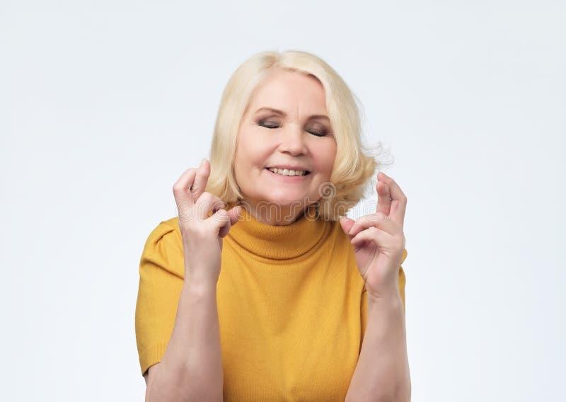 Mujer rubia mayor que cruza sus fingeres y que desea para la buena suerte fotografía de archivo libre de regalías