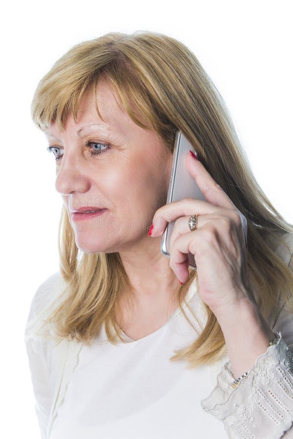 Mujer rubia mayor que habla en el teléfono foto de archivo