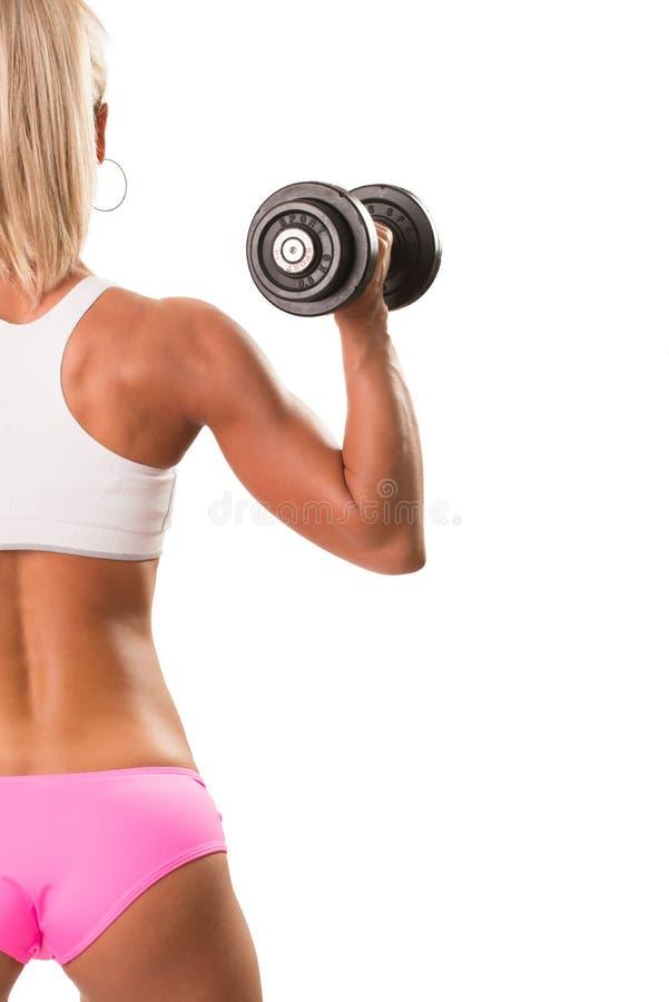 Mujer rubia muscular del retrato trasero de la visión que lleva a cabo pesa de gimnasia fotos de archivo libres de regalías