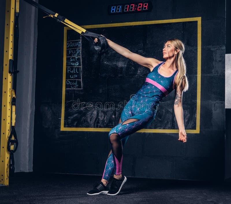 Mujer rubia muscular hermosa en ropa de deportes con un tatuaje en su brazo que hace ejercicio con el sistema de TRX en el gimnas imagenes de archivo