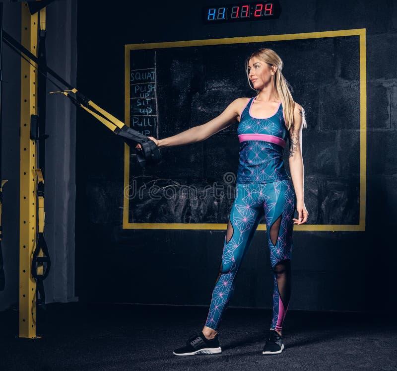 Mujer rubia muscular hermosa en ropa de deportes con un tatuaje en su brazo que hace ejercicio con el sistema de TRX en el gimnas imágenes de archivo libres de regalías