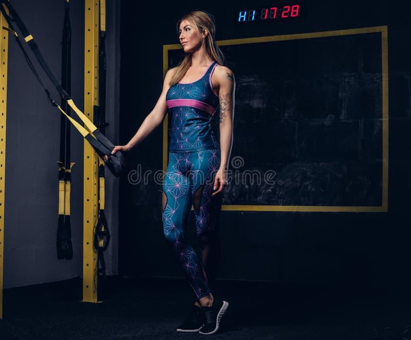 Mujer rubia muscular hermosa en ropa de deportes con un tatuaje en su brazo que presenta con el sistema de TRX en el gimnasio imagen de archivo