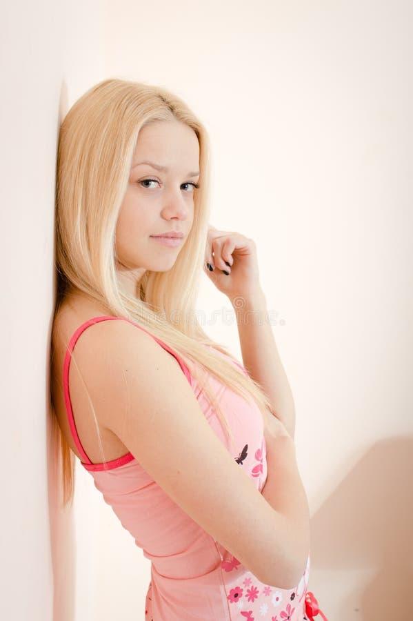 Mujer rubia natural atractiva atractiva joven de los ojos azules en los pijamas que colocan la pared cercana y que miran el retra fotografía de archivo