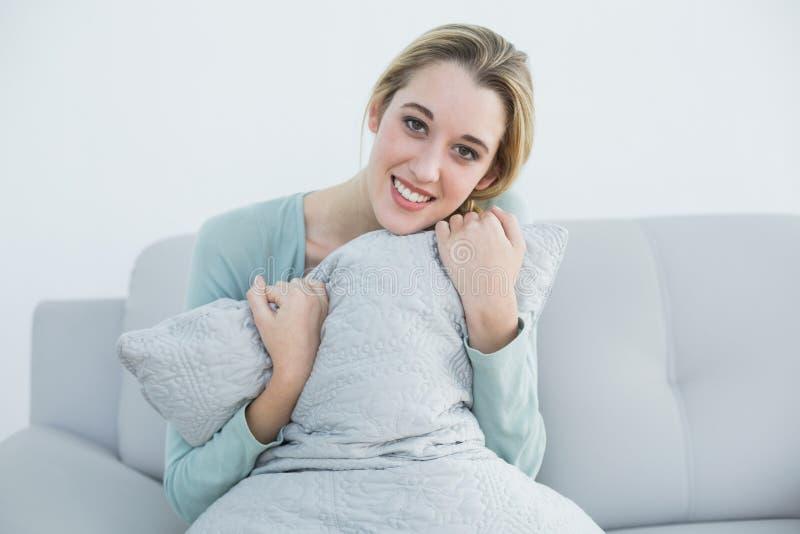 Mujer rubia pacífica que sostiene una almohada que se sienta en el sofá foto de archivo