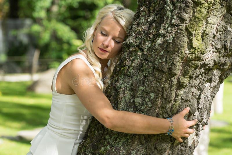 Mujer rubia que abraza un árbol en parque imagen de archivo