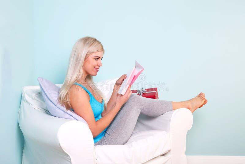Mujer rubia que abre una tarjeta de cumpleaños fotos de archivo libres de regalías