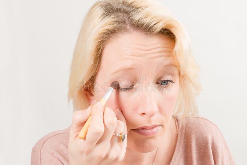 Mujer rubia que aplica el sombreador de ojos fotografía de archivo libre de regalías