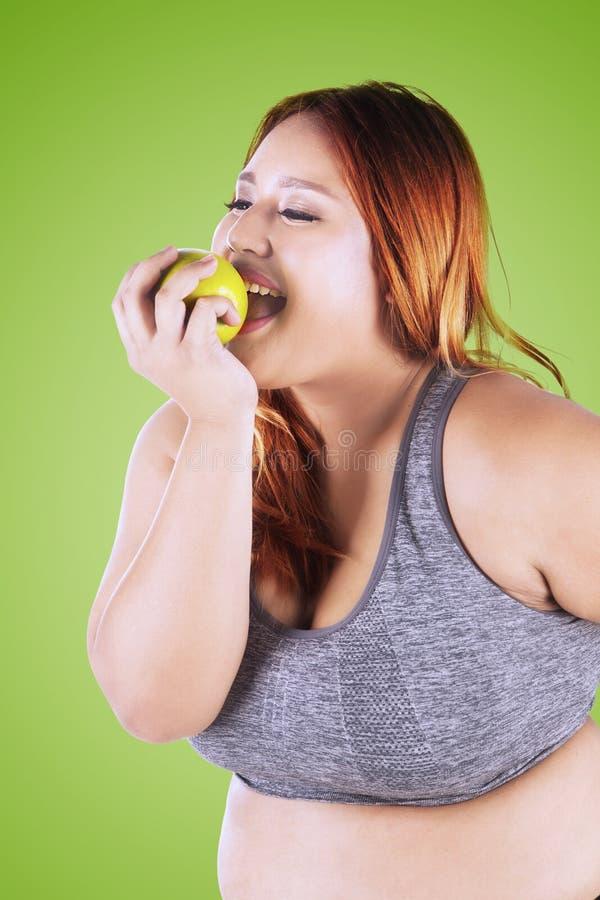 Mujer rubia que come la manzana en estudio imagen de archivo libre de regalías