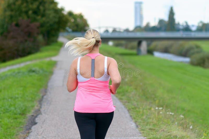Mujer rubia que corre a lo largo del río imagen de archivo