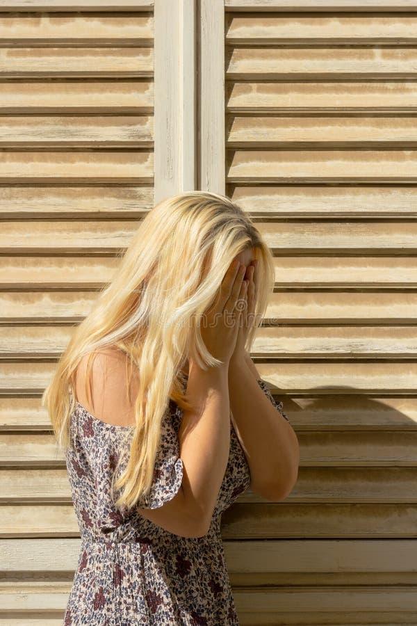 Mujer rubia que cubre su cara con las manos y que llora en persianas de ventana beige delanteras imagenes de archivo