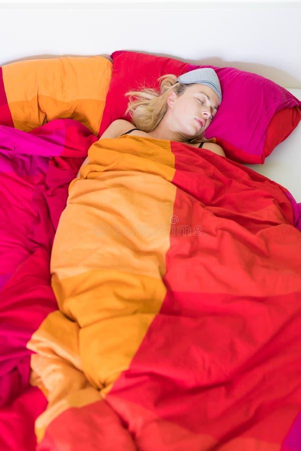 Mujer rubia que duerme en su cama colorida foto de archivo