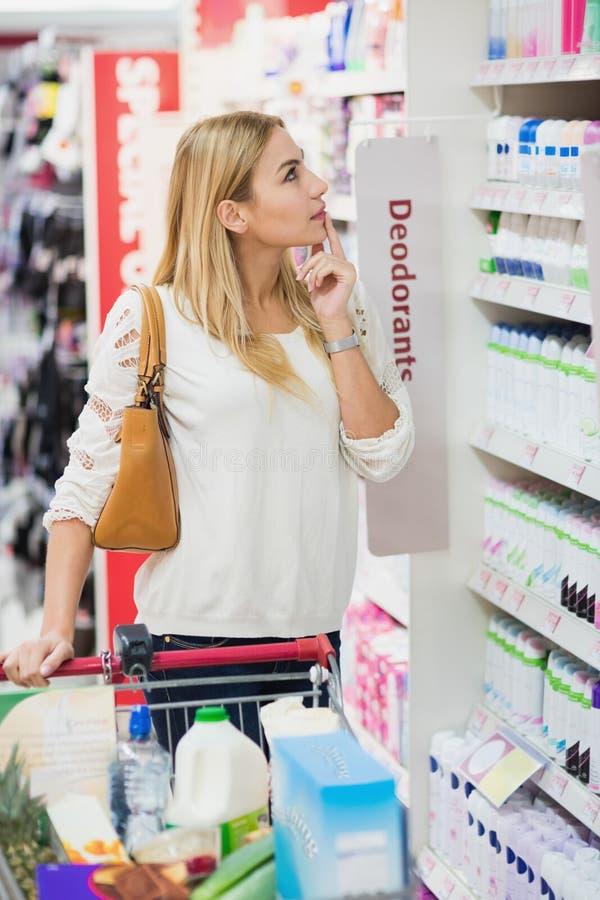 Mujer rubia que elige cuidadosamente el producto imagen de archivo libre de regalías