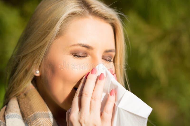 Mujer rubia que estornuda en tejido imágenes de archivo libres de regalías