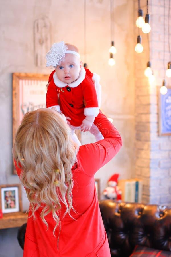 Mujer rubia que guarda al bebé femenino el llevar de la ropa roja foto de archivo