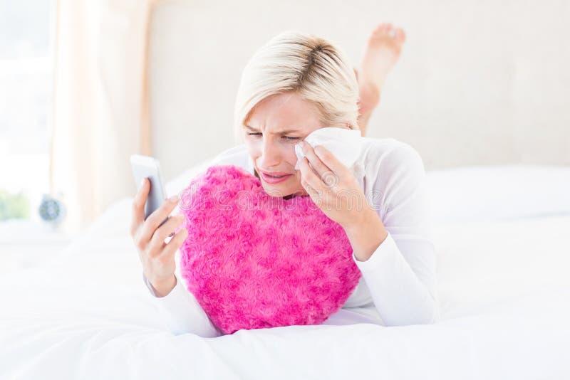 Mujer rubia que lleva a cabo su teléfono móvil y griterío fotos de archivo