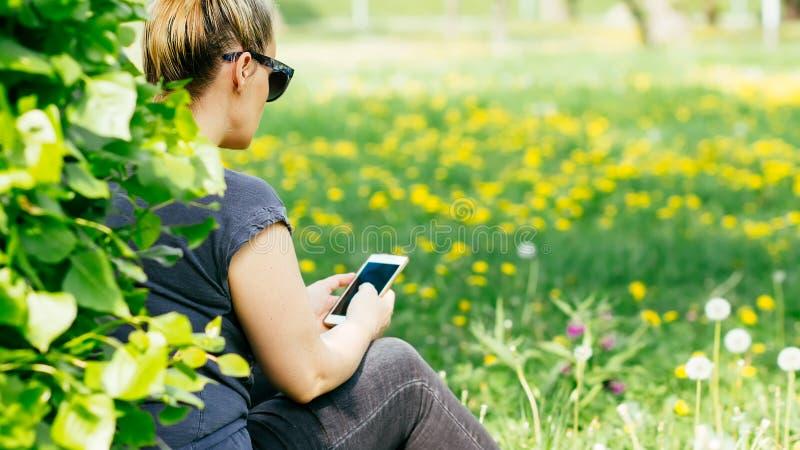 Mujer rubia que manda un SMS en el campo de flores por el árbol fotos de archivo libres de regalías