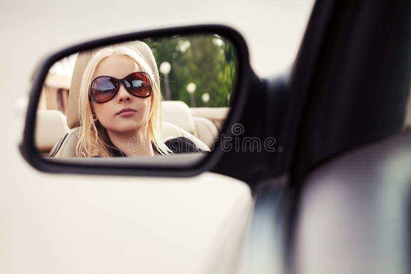 Mujer rubia que mira en el espejo de la vista posterior del coche imágenes de archivo libres de regalías