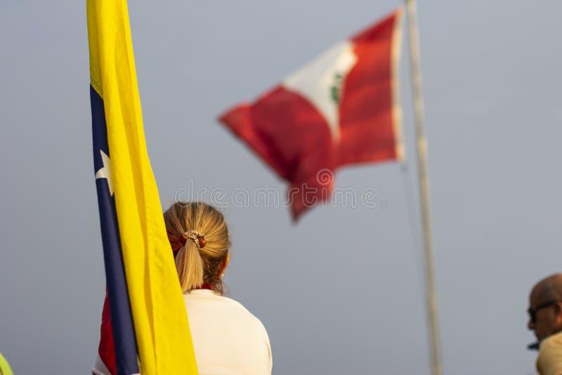 Mujer rubia que mira la bandera peruana mientras que sostiene la bandera venezolana foto de archivo