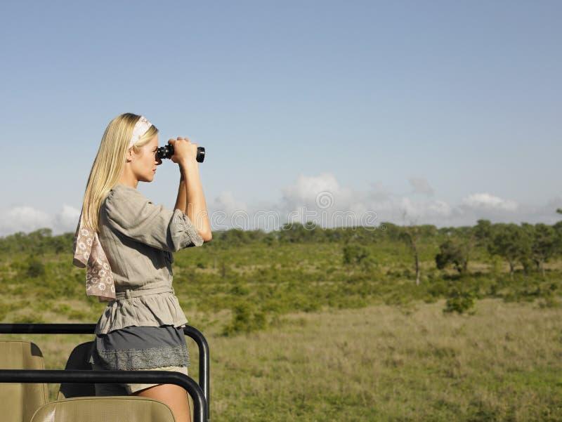 Mujer rubia que mira a través de los prismáticos en jeep foto de archivo libre de regalías