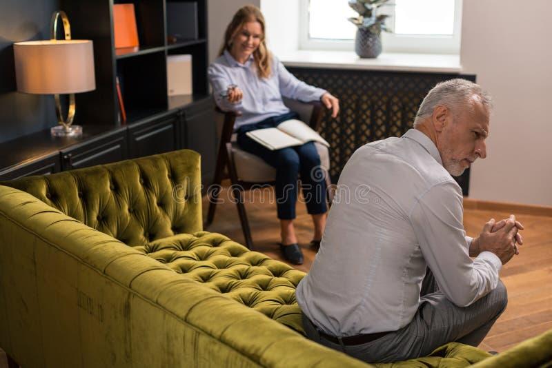Mujer rubia que mira a un hombre gris-cabelludo serio foto de archivo libre de regalías