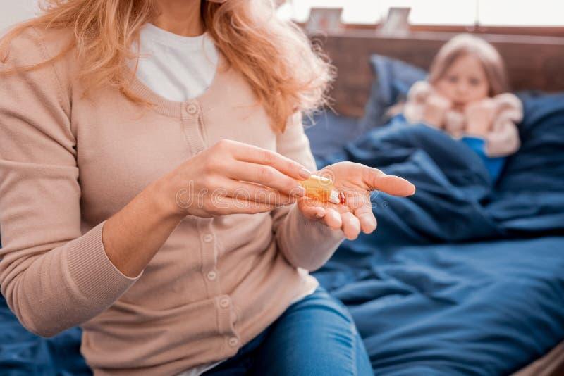 Mujer rubia que prepara las píldoras para una hija imagen de archivo libre de regalías
