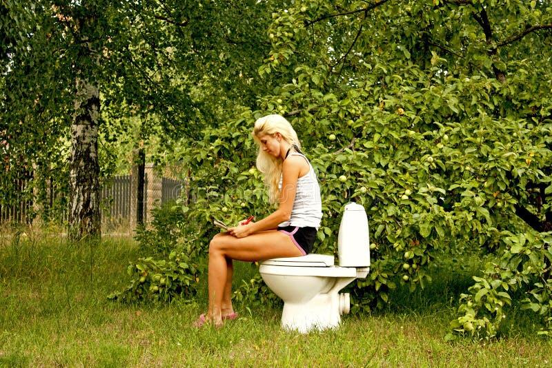 Mujer rubia que se sienta en una taza del inodoro y que lee un libro fotos de archivo