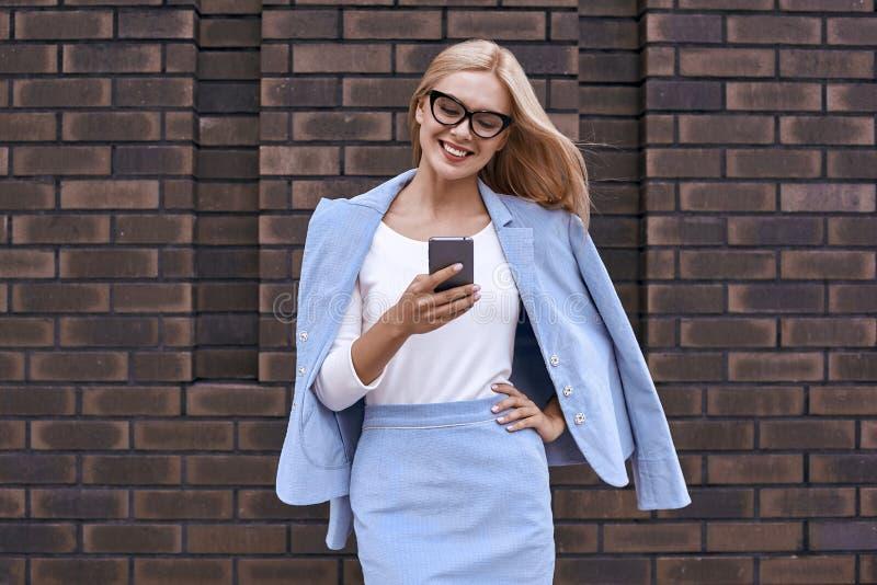 Mujer rubia que sonríe en su teléfono, feliz fotos de archivo libres de regalías